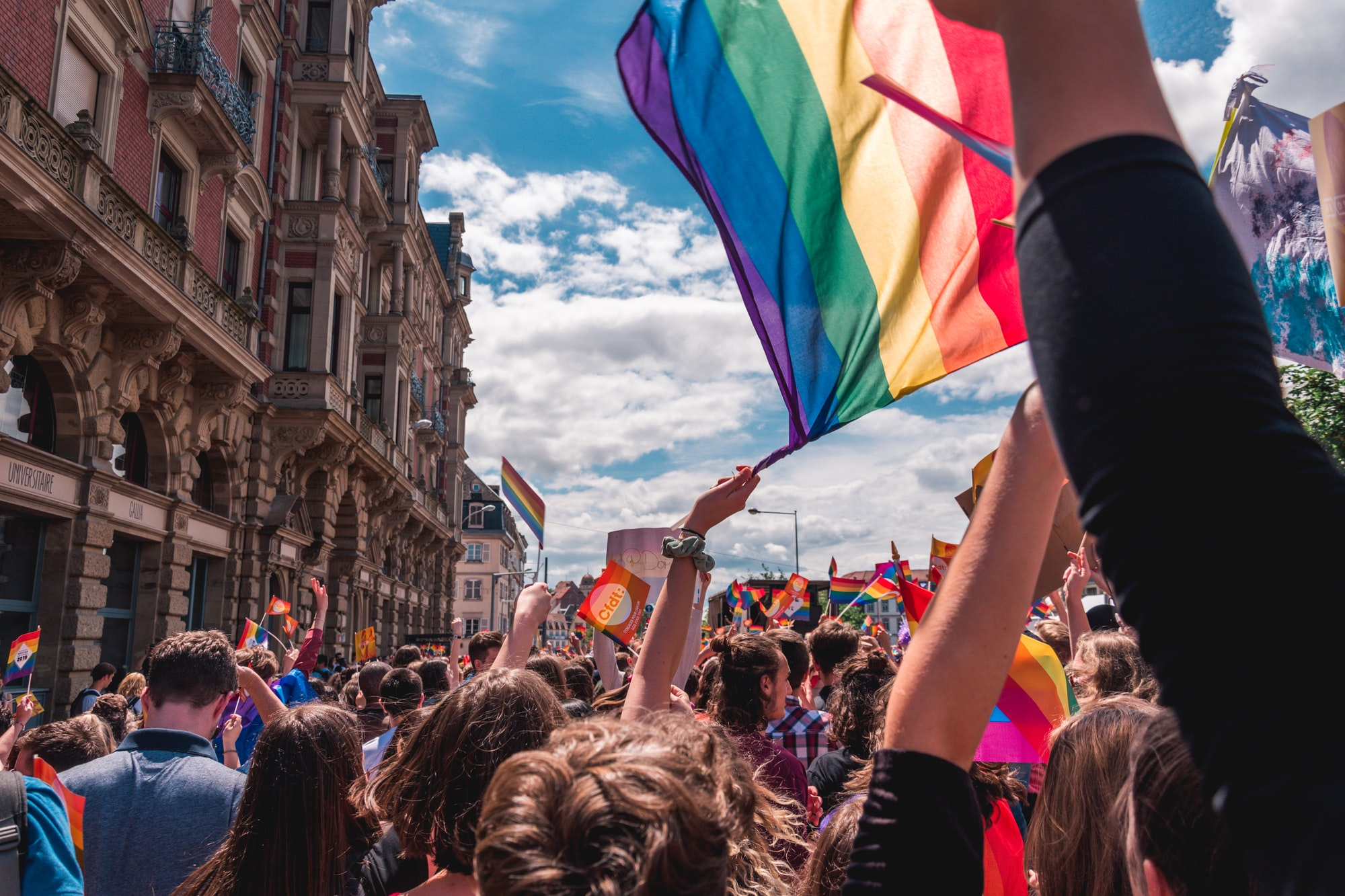 Crowd of people at a LGBTQIA+ rights parade. In the center of the photograph there is an individual holding a pride flag.
