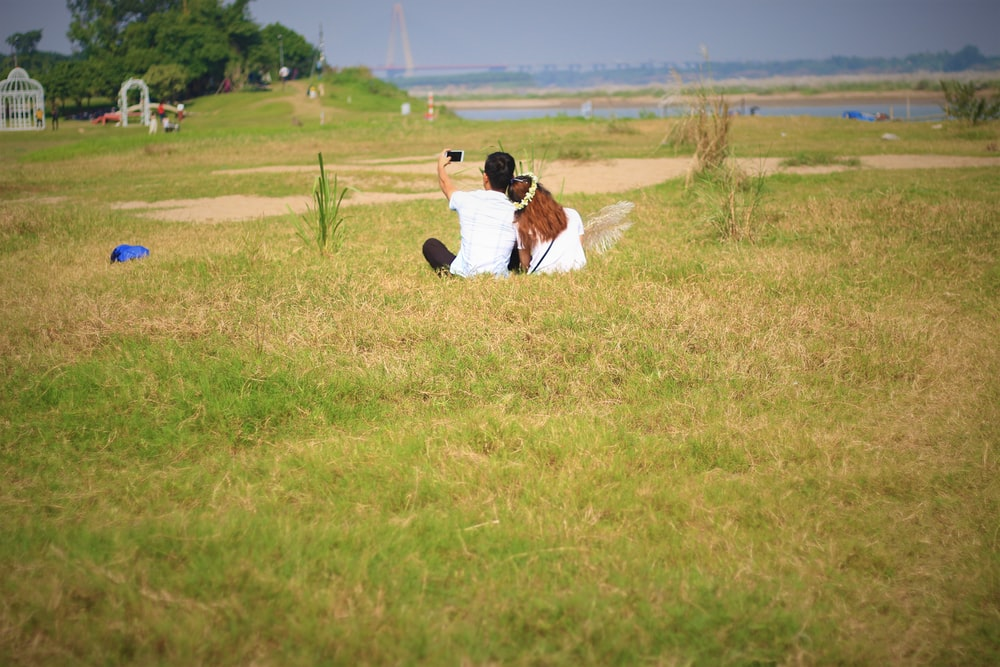 man and woman sitting on field