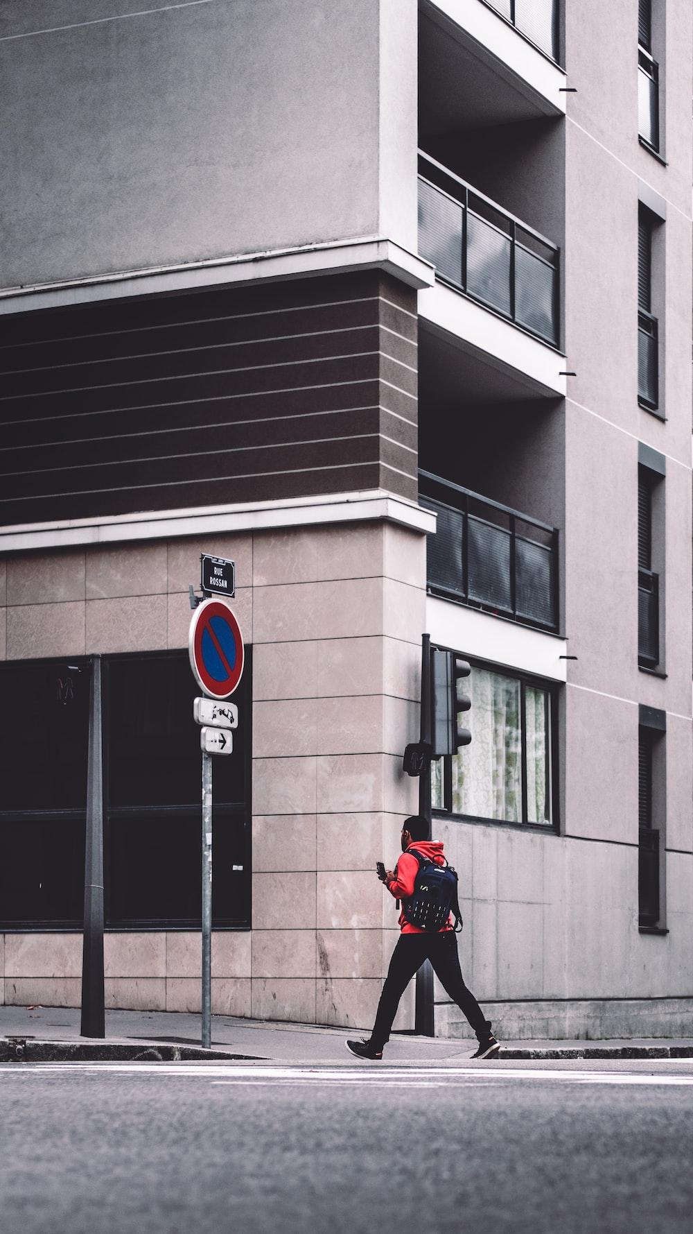 man walking on sidewalk beside signboard and building
