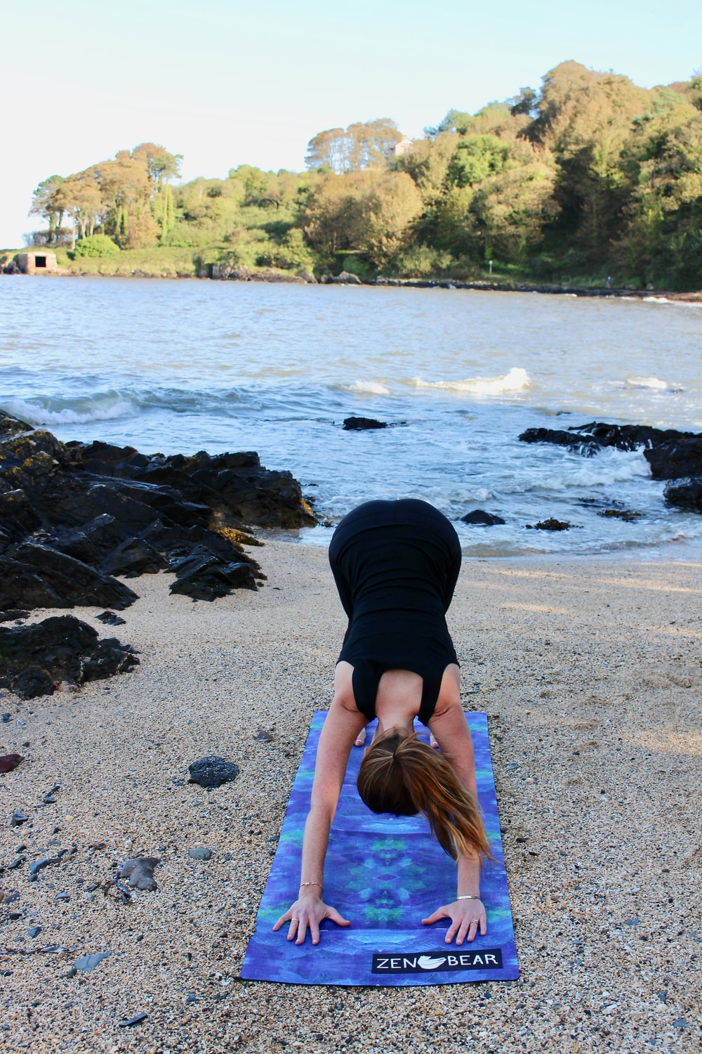 woman in black outfit doing yoga beside body of water