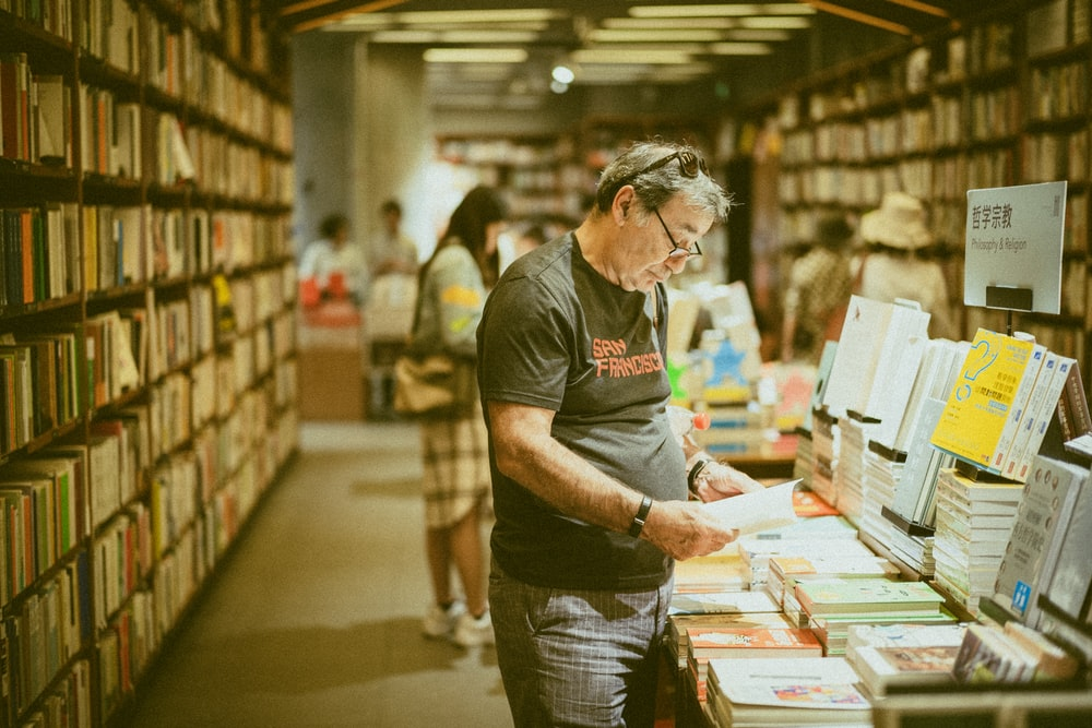 selective focus photography of standing person holding book