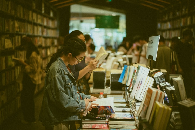 A photo of people in a bookstore, browsing the shelves.