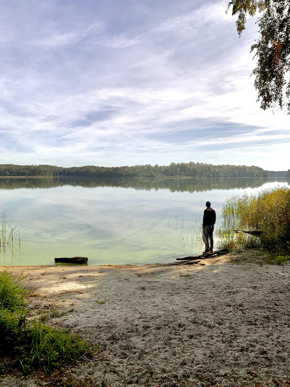 man standing front of lake during daytime