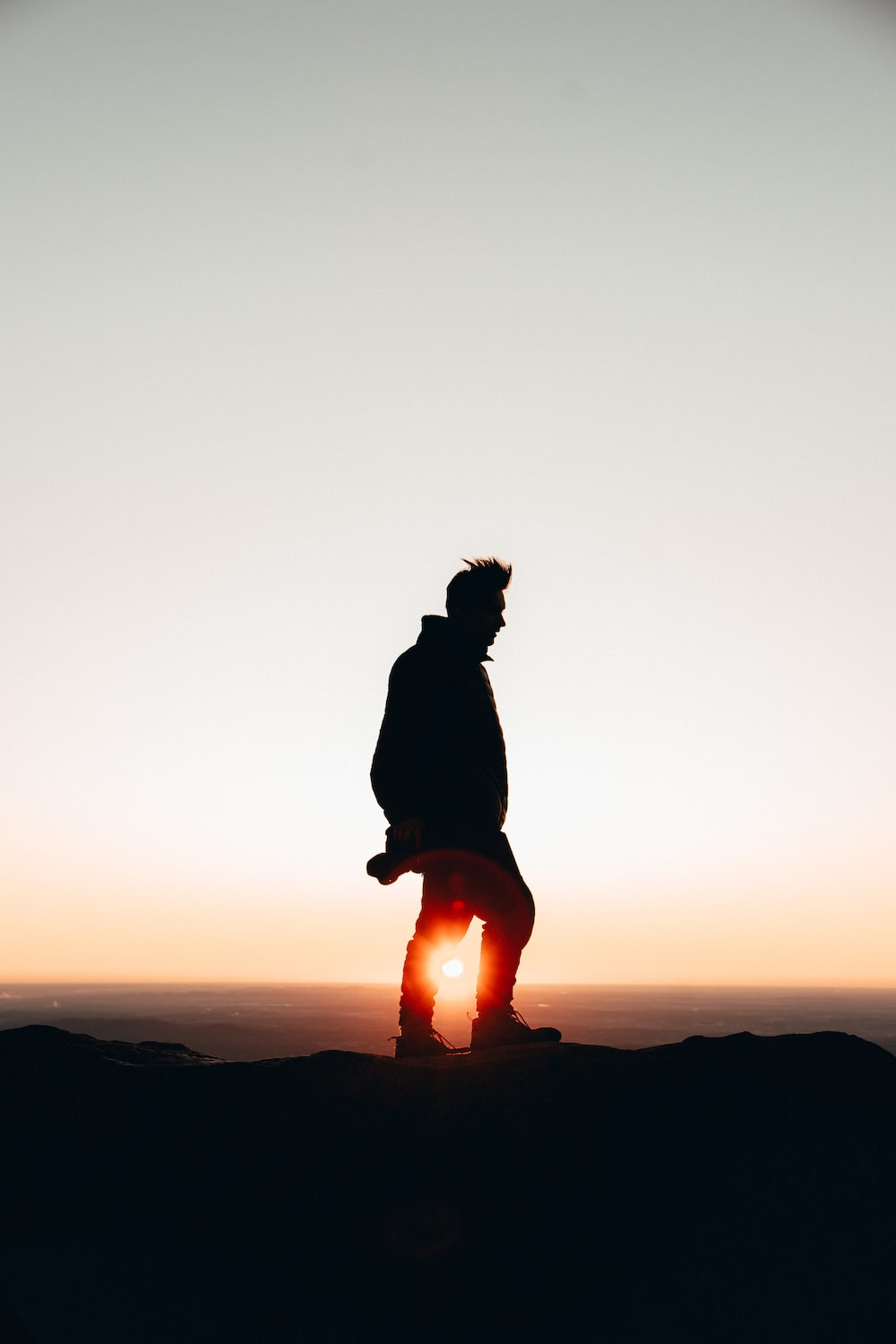 silhouette of man standing on cliff during golden hour