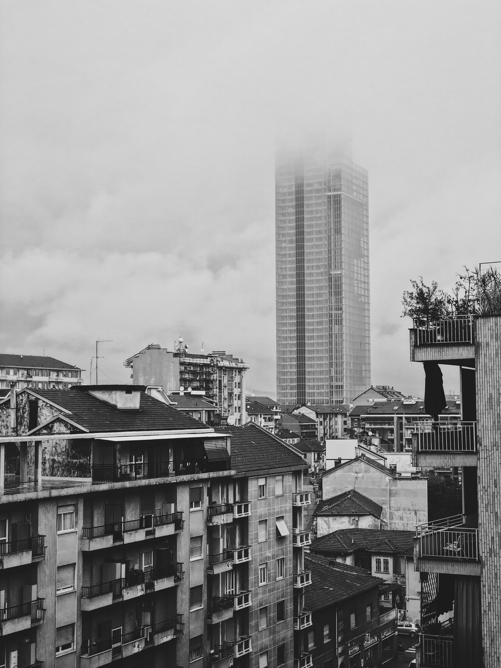 grayscale photography of city with high-rise buildings and houses
