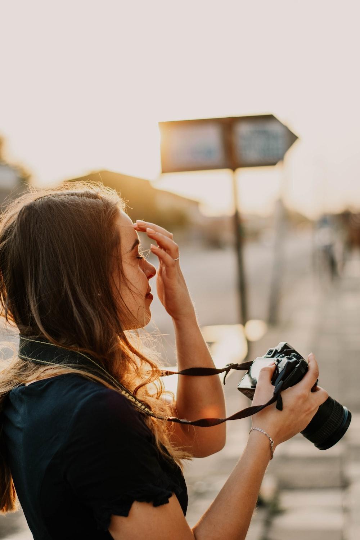 woman in black shirt holding DSLR camera