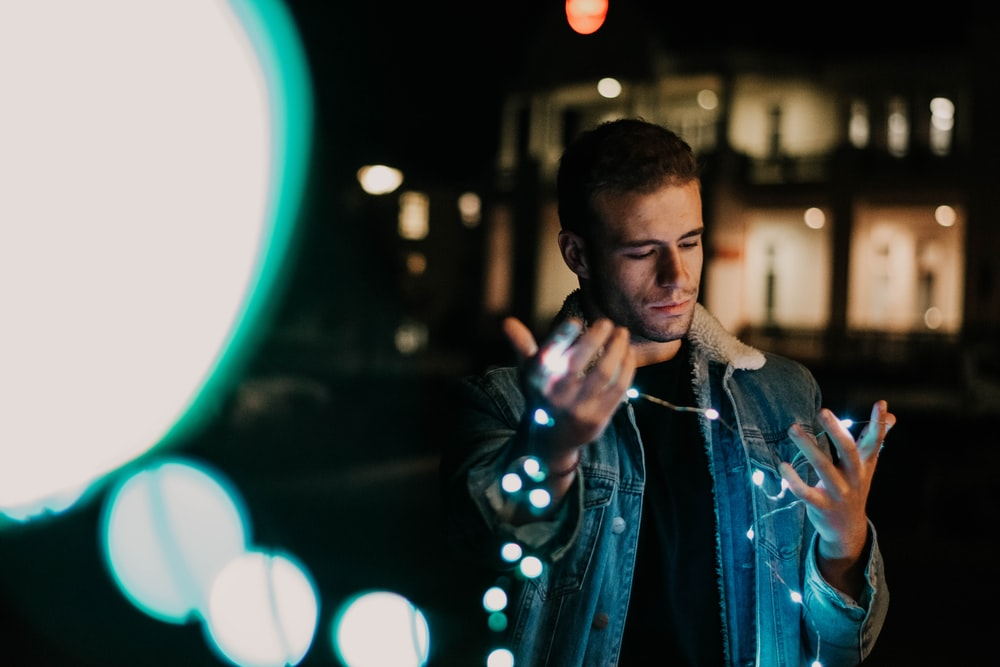 man in blue denim jacket holding string lights