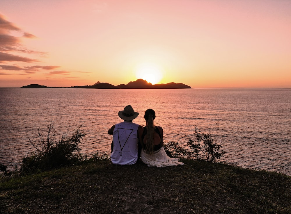 man and woman wearing on grass field looking at sunset behind og silhouette mountain