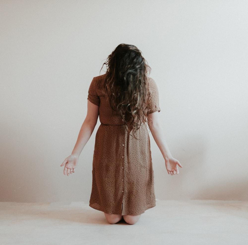 kneeling woman wearing brown dress