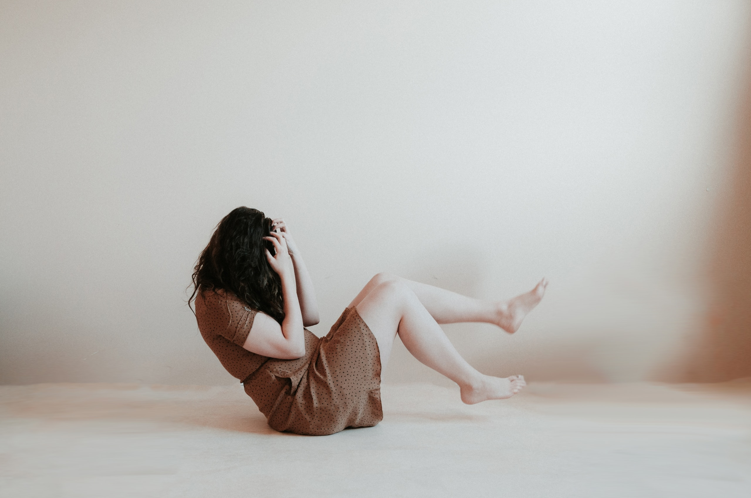 ansiedad, woman sitting on floor wearing brown dress
