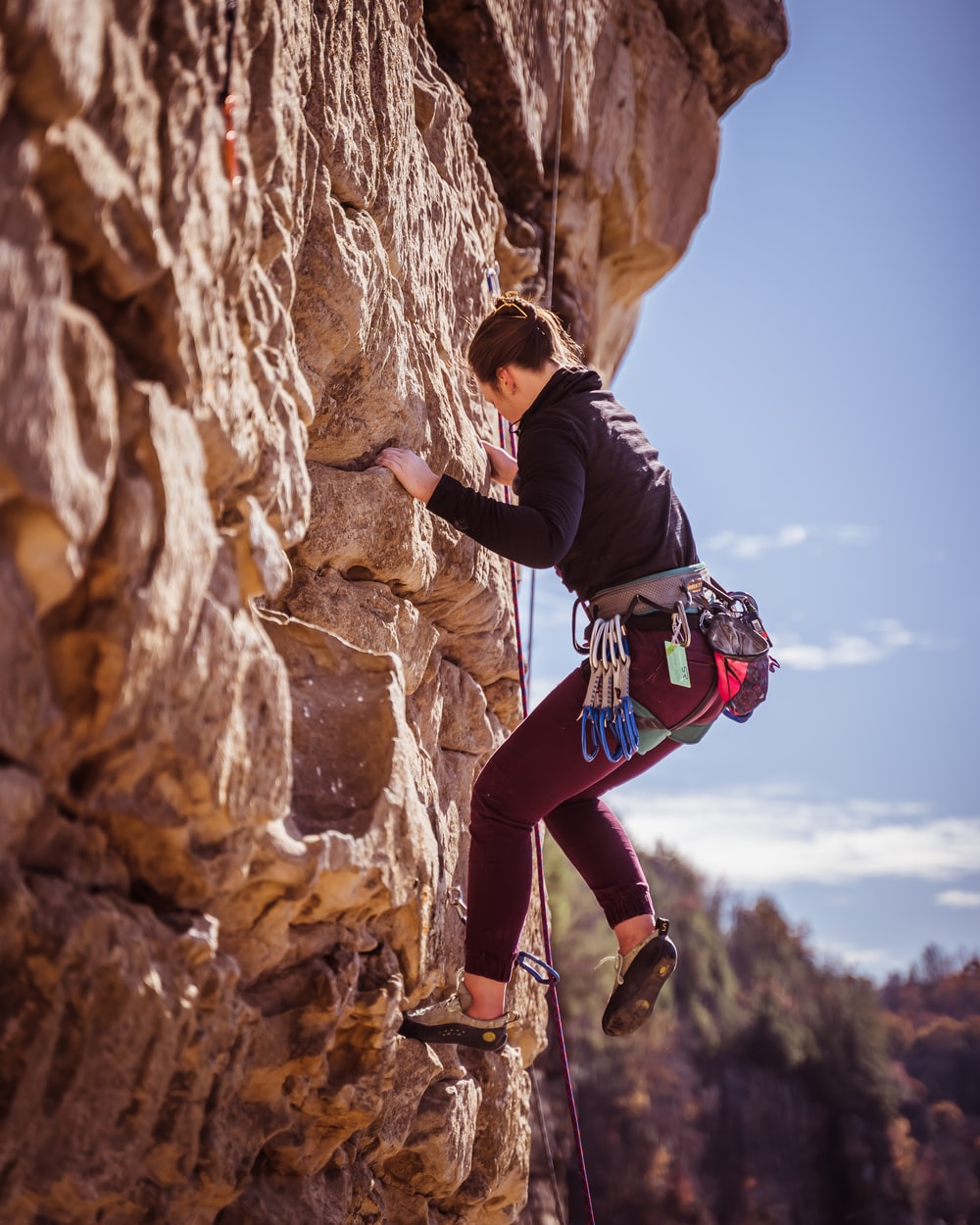woman climbing on rock formation