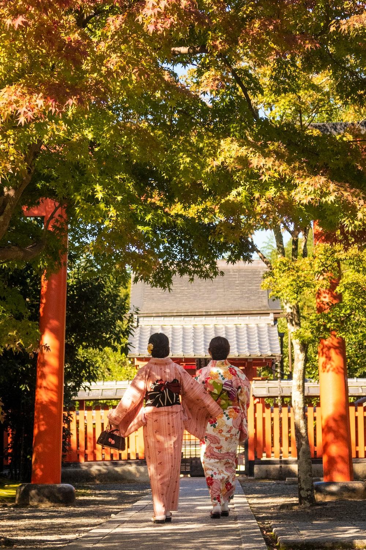 women in dresses walking bear trees