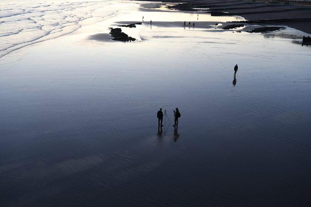 three person standing on seashore