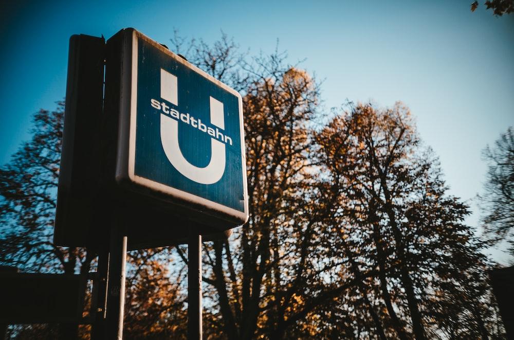 trees beside blue Stadtbahn signage