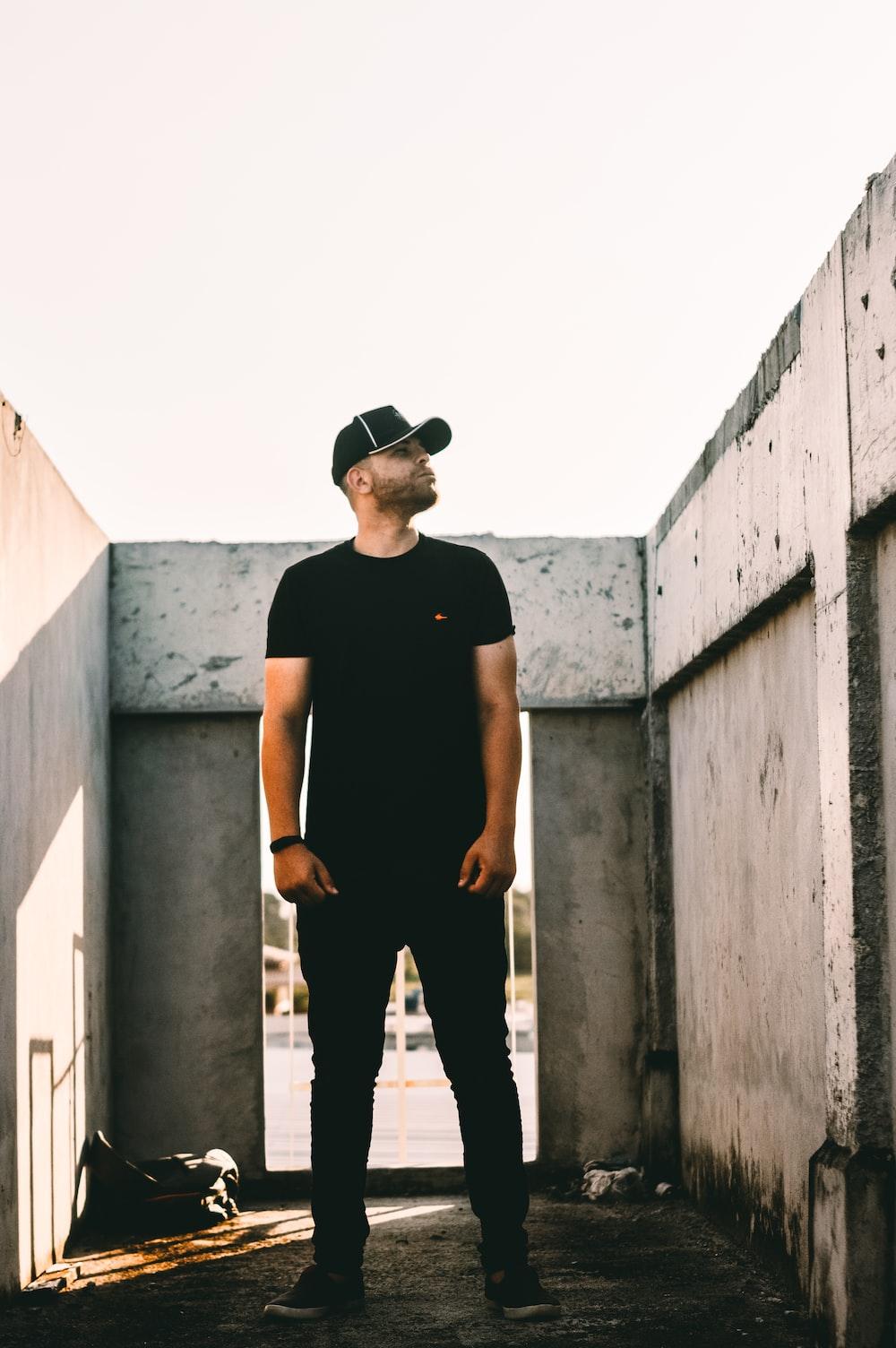 man wearing black t-shirt and black denim jeans