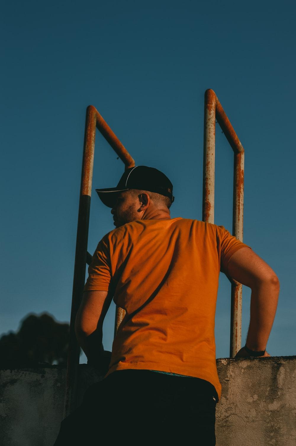 man in brown t-shirt standing beside wall