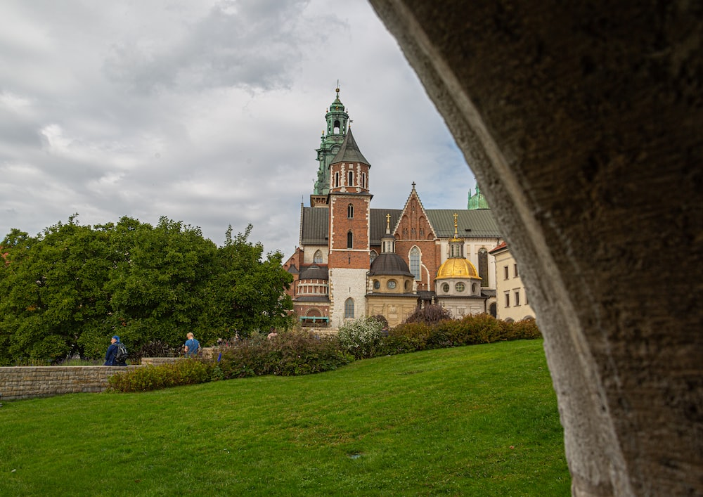 few people walking near Wawel Cathedral in Krakow Poland under white and blue sky during daytime