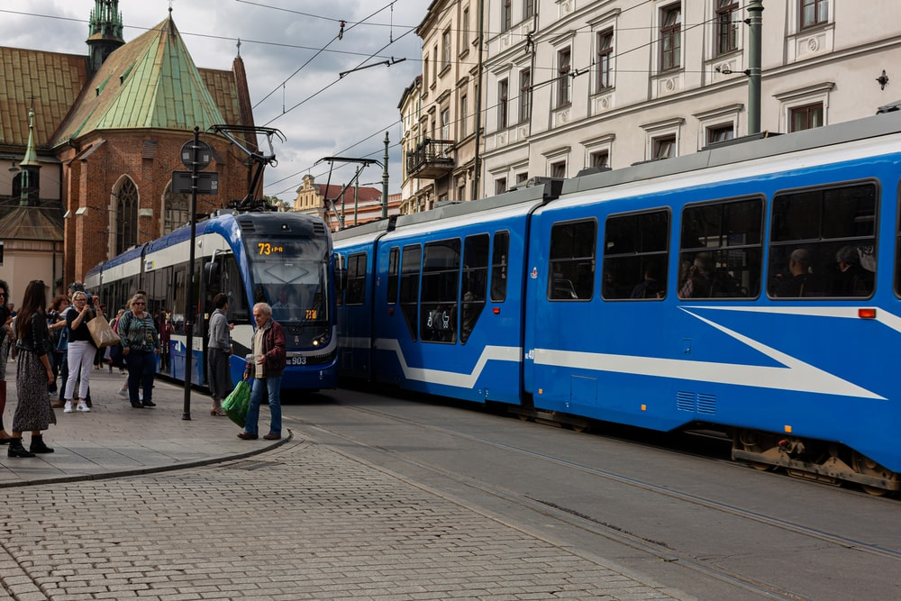people walking near blue and white train under white and blue sky during daytime