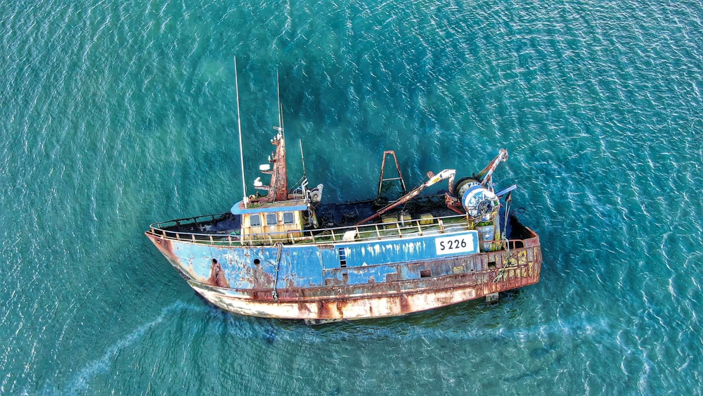 blue and brown fishing boat on sea