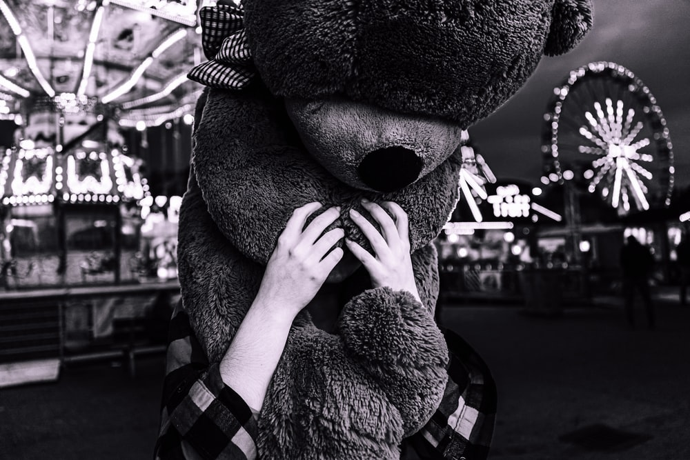 person holding bear plush toy