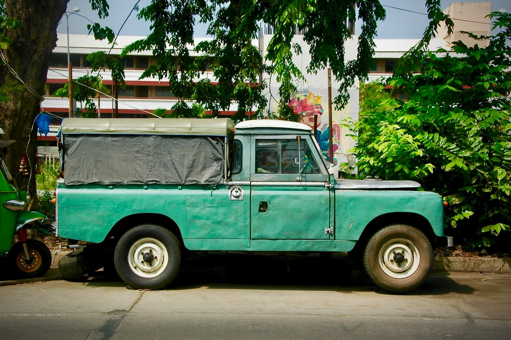 parked teal single cab pickup truck beside tree