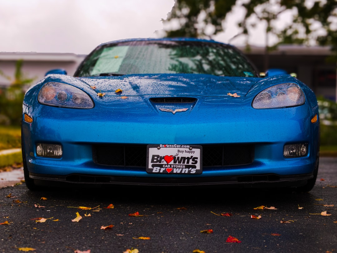 A blue Late Model Corvette just after the rain with fallen leaves on the pavement.