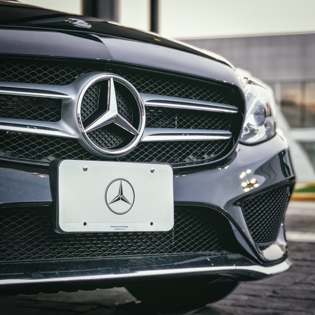 A black Mercedes Benz sits in front of a dealership in Fairfax VA.