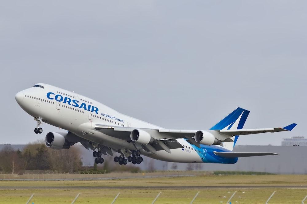 white and blue Corsair passenger plane flying on runway