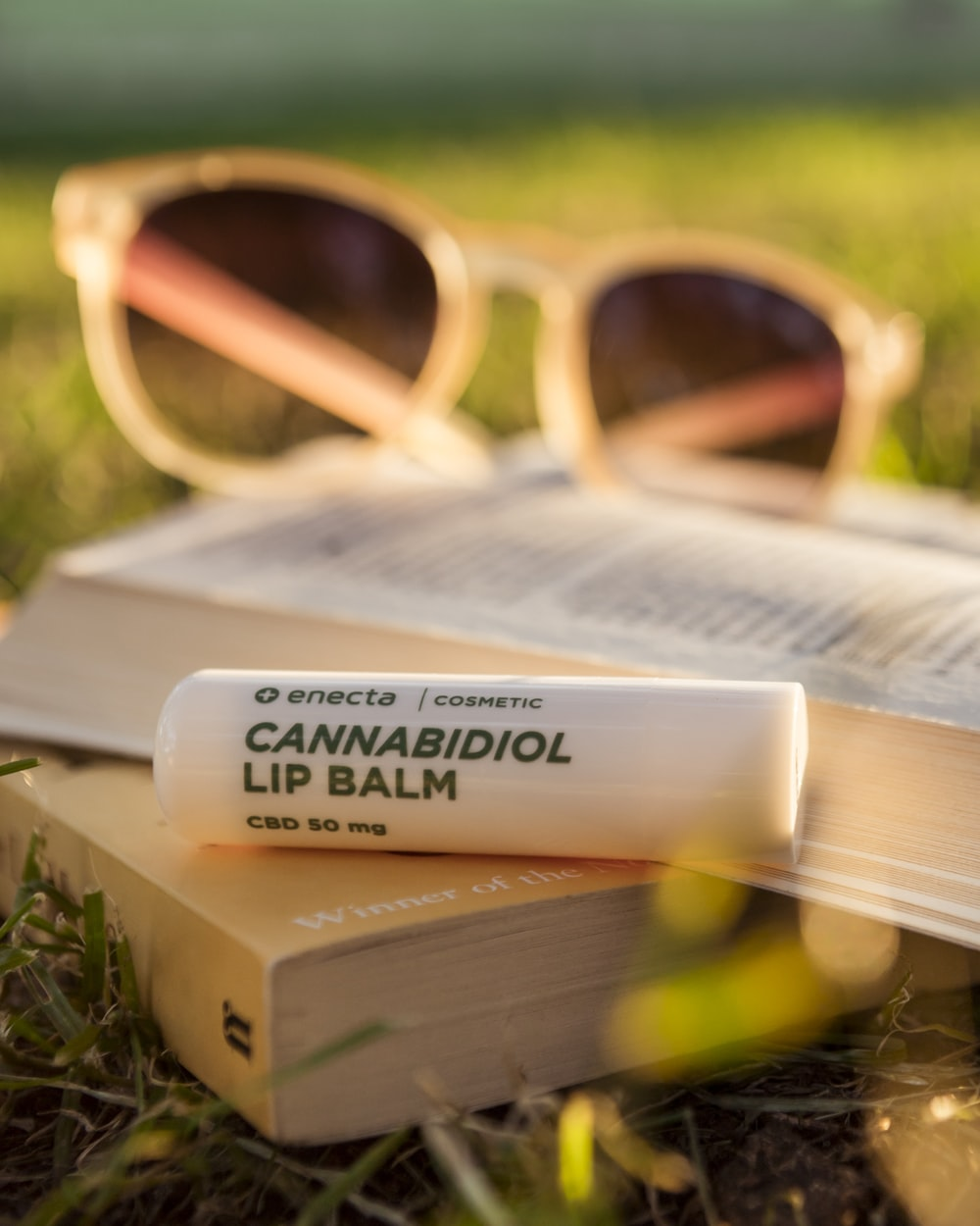 Cannabidiol lip balm on book on grass during daytime