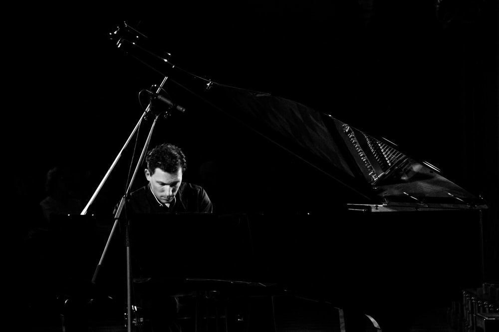 grayscale photo of man playing classic piano