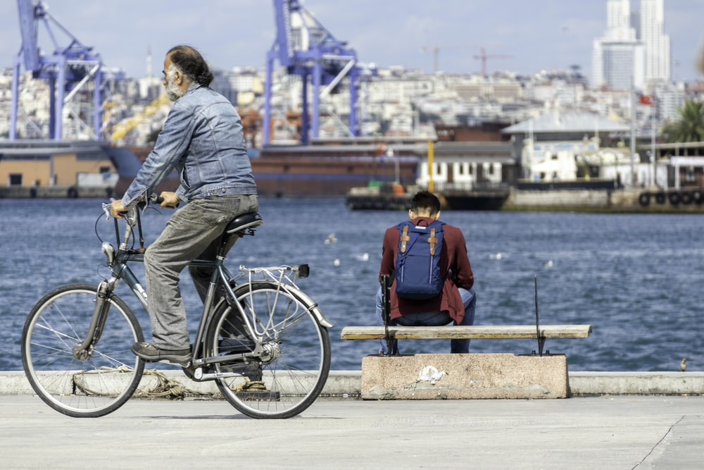 man riding bicycle near body of water