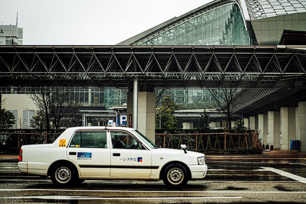 white taxi sedan on roadway