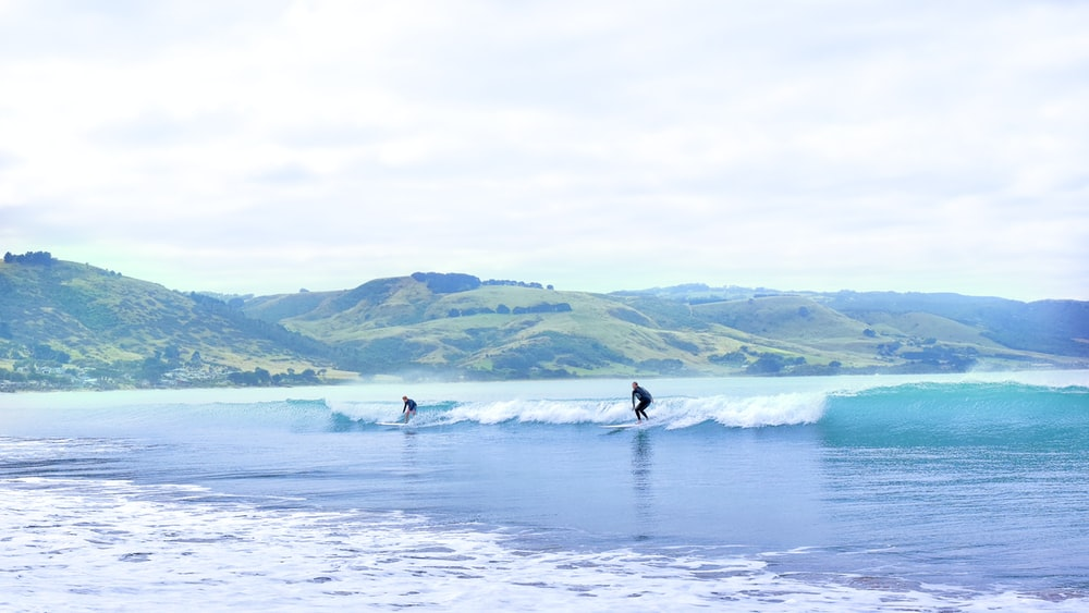 two person surfing on sea