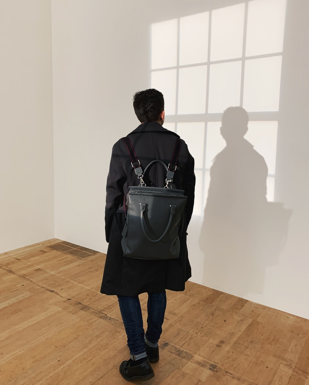 man wearing black leather backpack standing near the wall