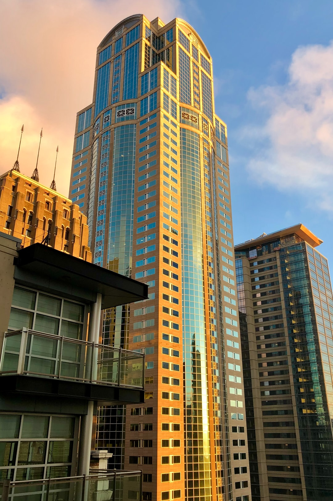 """Left to right, ornamental spires atop the Seattle Tower (formerly Northern Life Tower), 1201 Third Avenue Building (formerly Washington Mutual (WaMu) Tower), and the newly constructed """"2 + U"""" building at 2nd and University.  In the foreground, left, the balconies of a modern penthouse atop The Cobb Apartments."""