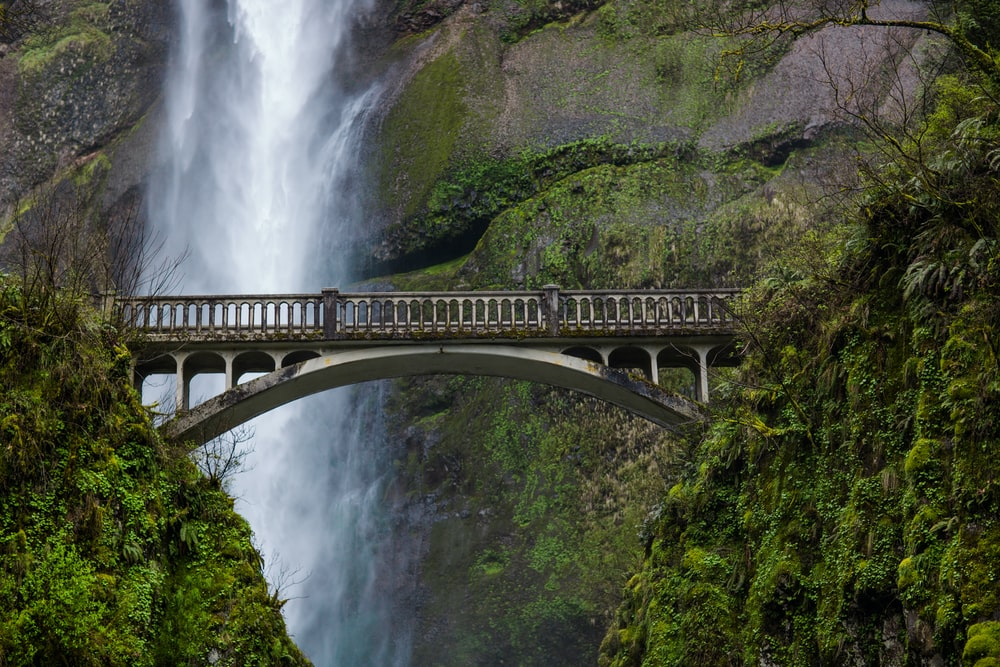 gray metal bridge beside waterfalls