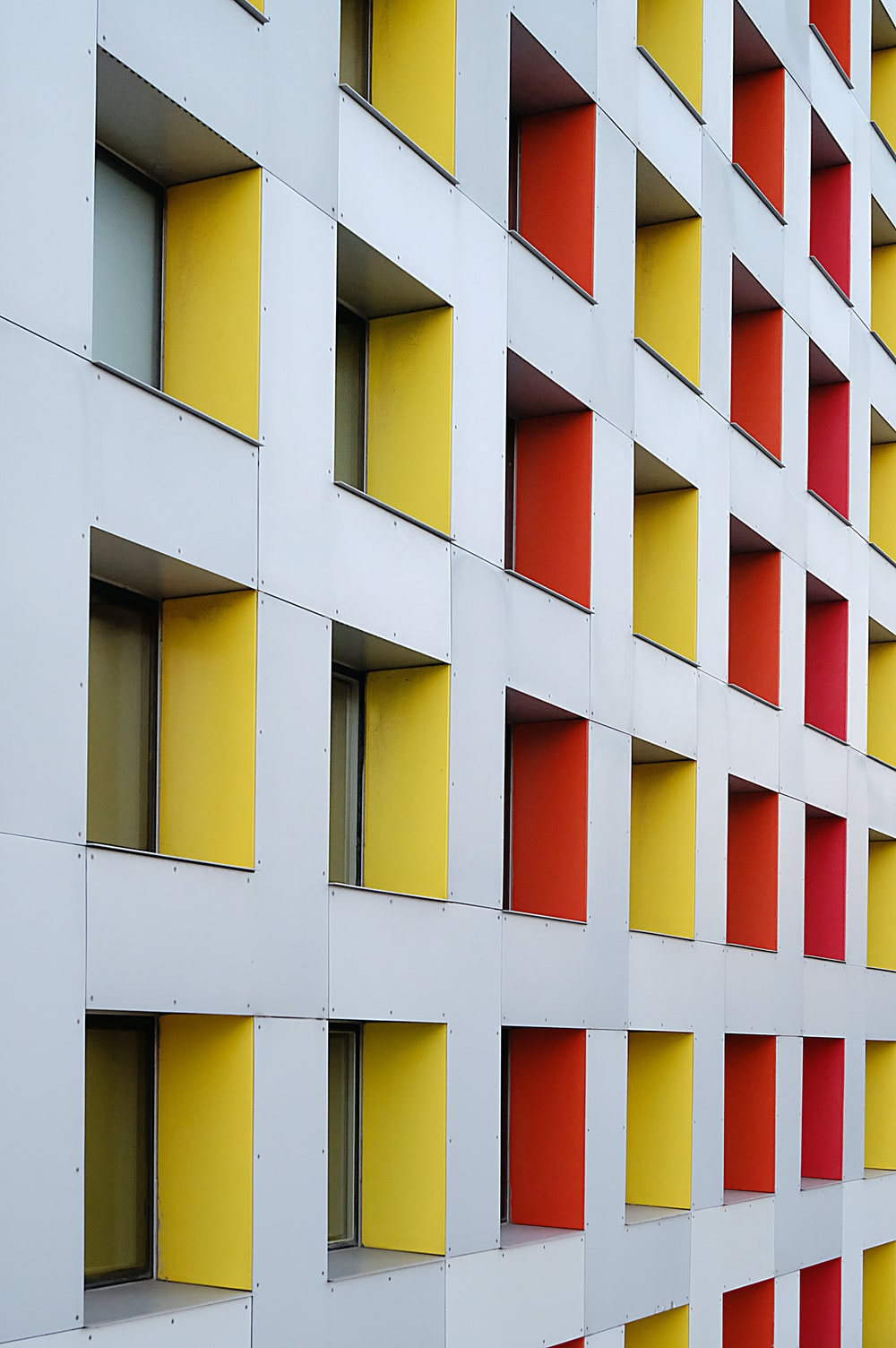 white, yellow, and red concrete multi-storey building