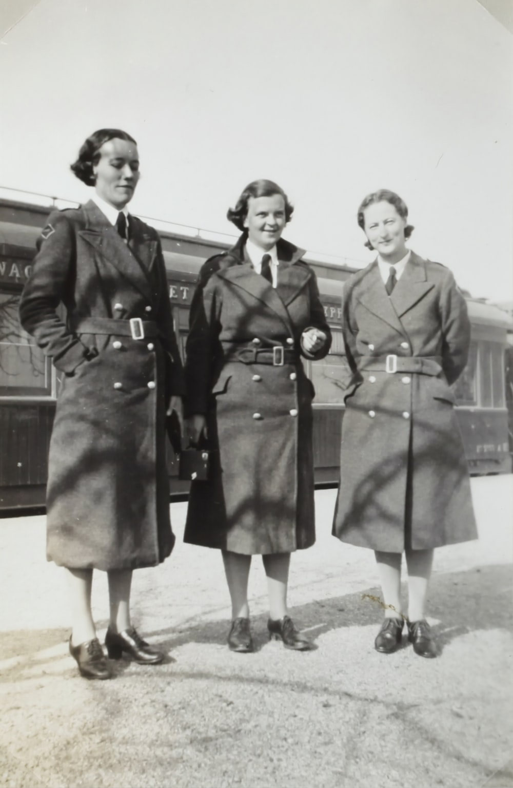 grayscale photo of three women in coats