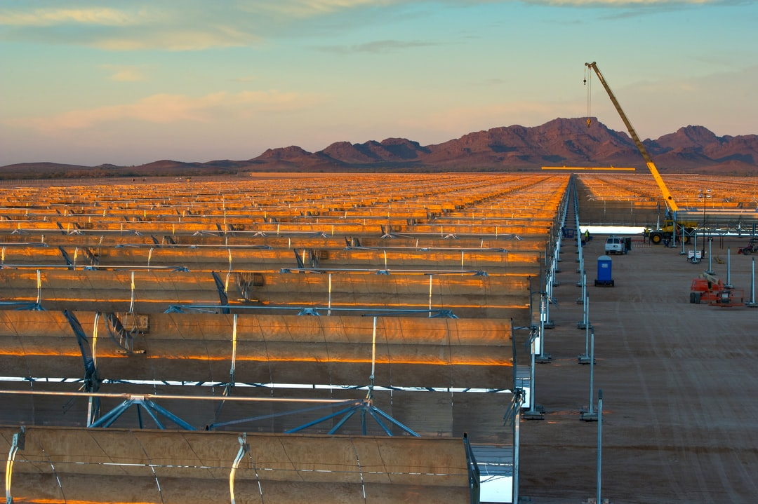 Workers installing mirrored parabolic trough collectors. Workers construct one of a dozen thermos like molten salt tanks at Abengoa's Solana Plant. Thermal storage will provide up to 6 hours of dispatchable energy to be used after sunset of if cloudy. The molten salt will generate electricity with conventional steam turbines. Solana is a 280 megawatt utility scale solar power plant (CSP) under construction in Gila Bend, Arizona, USA. When finished it will generate 280MW's providing over 70,000 Arizona homes with clean, sustainable power.