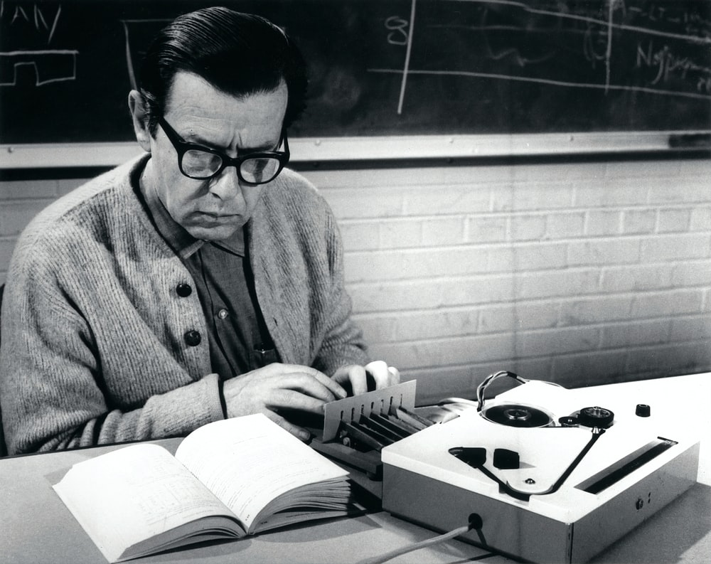 man holding device while reading book