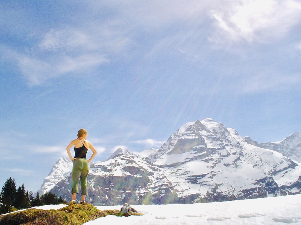 woman with both arms akimbo standing on grass rock on snow field near glacier mountains