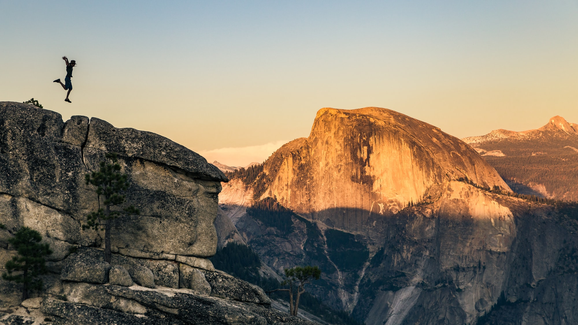 Silhouette of a man jumping on the edge of a cliff in front of the Half Dome of Yosemite National Park.