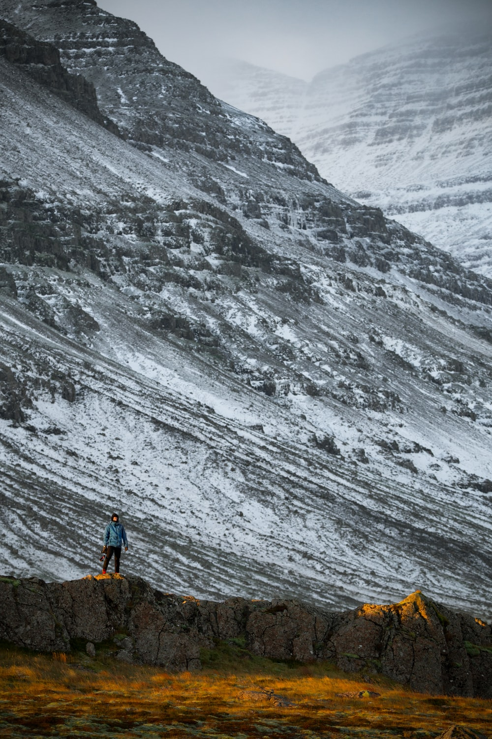 person standing beside grey mountain during daytime
