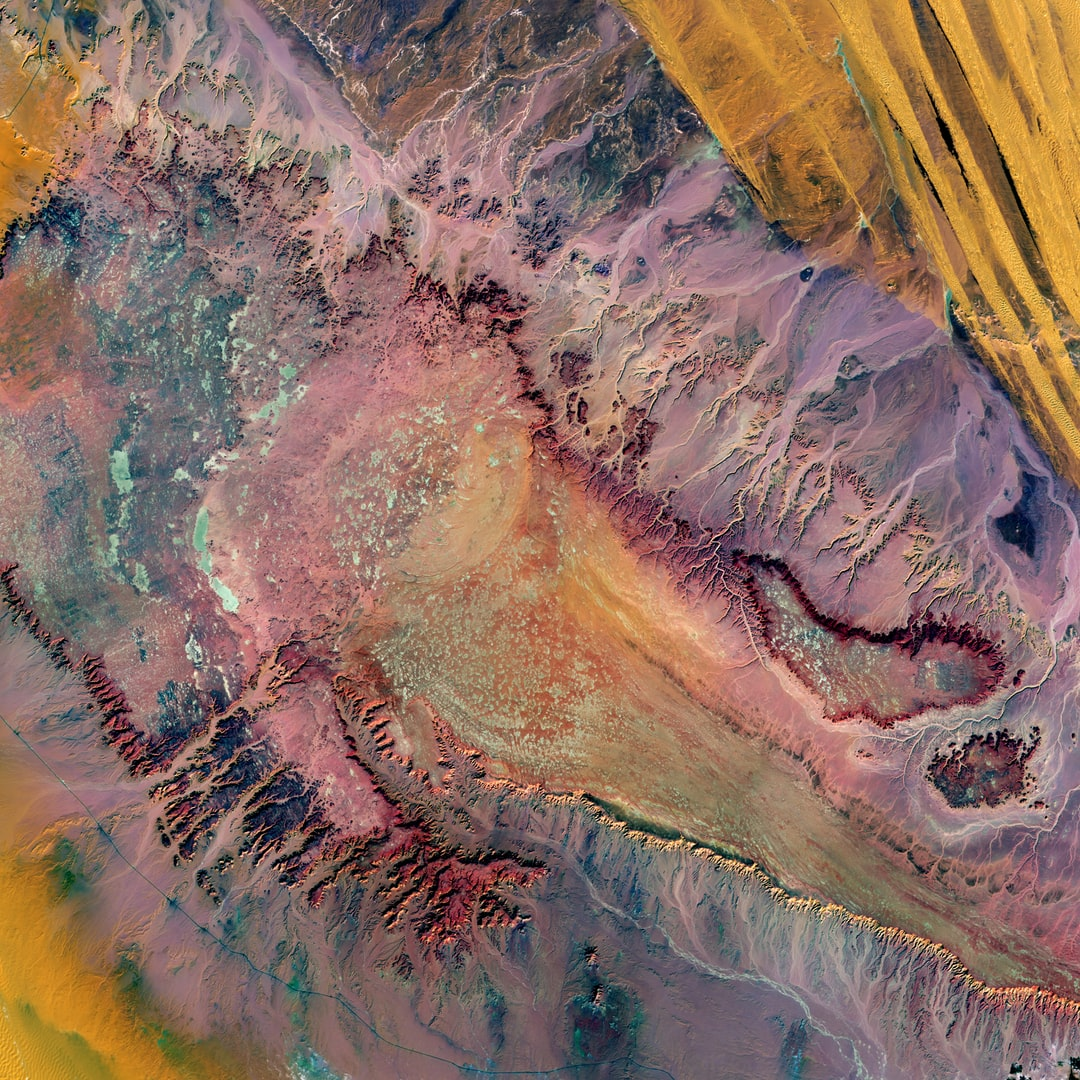 In a remote part of the Western Desert in central Egypt, highly eroded plateaus rise from the desert floor. The bright speckles are ancient dry lakes, the salt deposits reflecting brightly. Long ago, water flowed off the plateau, forming the breaches seen on the plateaus' edges. This desolate land between oases is surrounded by extensive sand dunes.