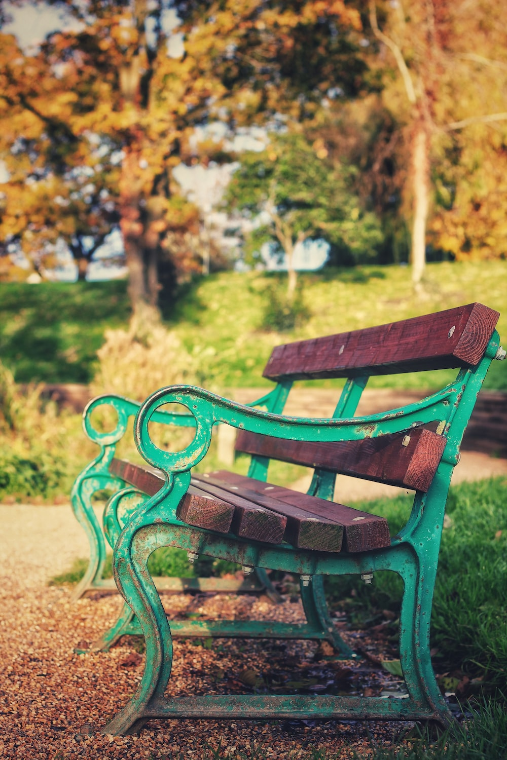 brown wooden and green metal bench