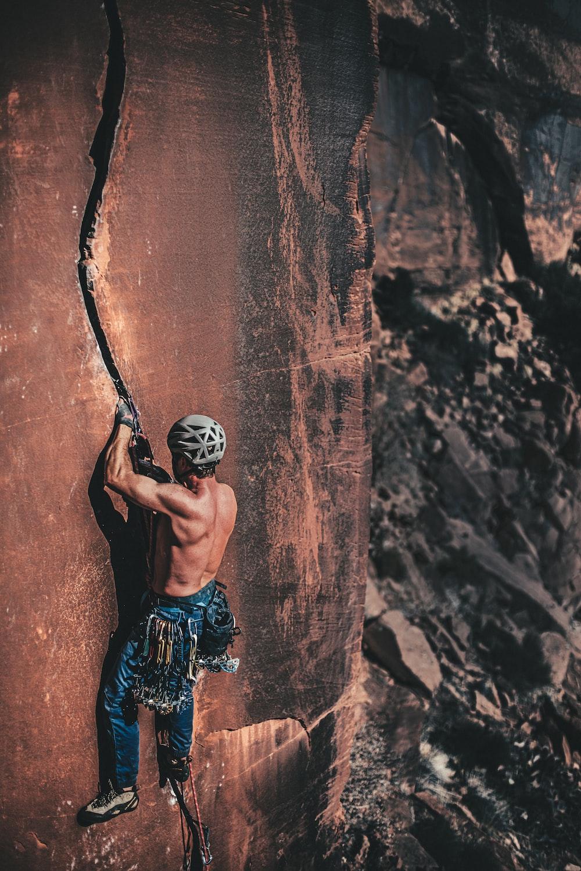 topless man rock climbing