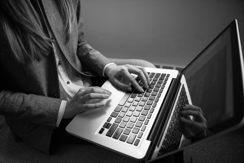 grayscale photography of woman typing on a laptop