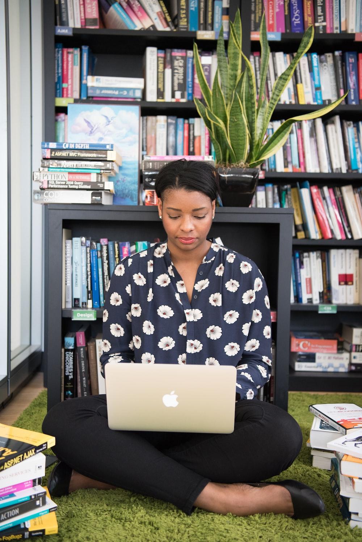 woman sitting on rug using MacBook