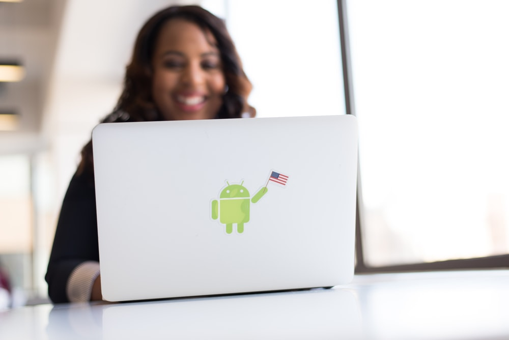 woman using laptop with android sticker