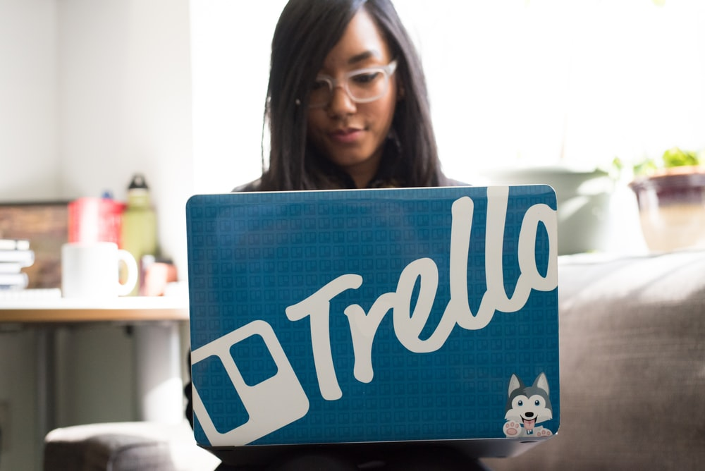 woman using laptop with blue and white trello sticker